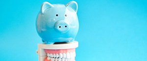 blue piggy bank atop model teeth signifying cost of dental implants in Agawam