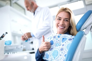 A young woman sitting upright in the dentist's chair and giving a thumbs up while the dentist prepares to perform air abrasion
