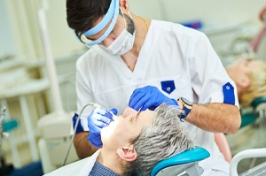 A male patient undergoing dental work after receiving painless local anesthesia