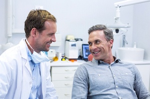 A male dentist talking to a male patient about his upcoming procedure