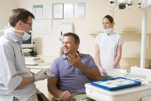 smiling man in dental chair talks to dentist