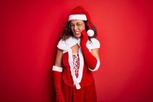 woman in Santa suit with a toothache