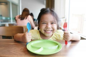 child smiling and sitting at a table with a fork and spoon in their hands