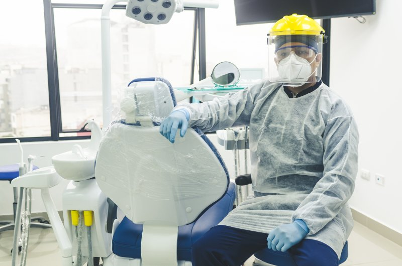 a dentist wearing personal protective equipment and preparing to see a patient