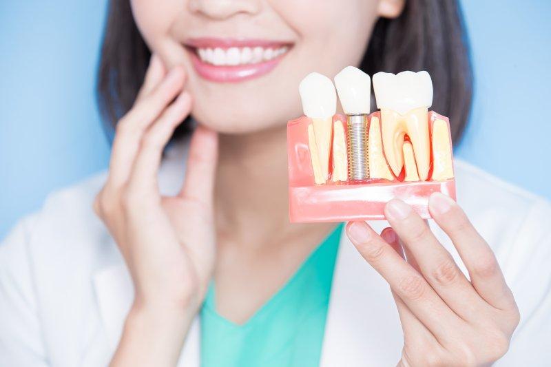 dentist holding dental implant model and smiling