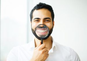 man showing off the results of his teeth whitening after braces with a magnifying glass